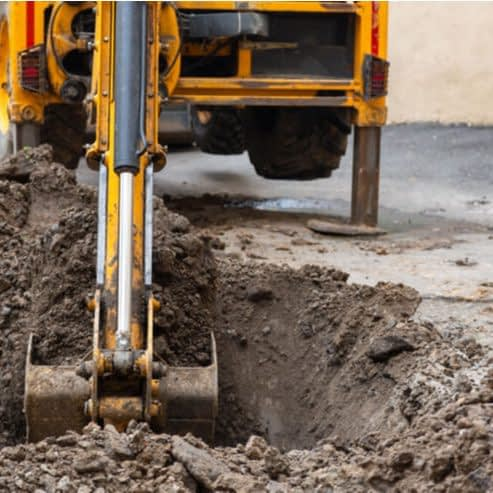 excavator digs a trench in a residential area